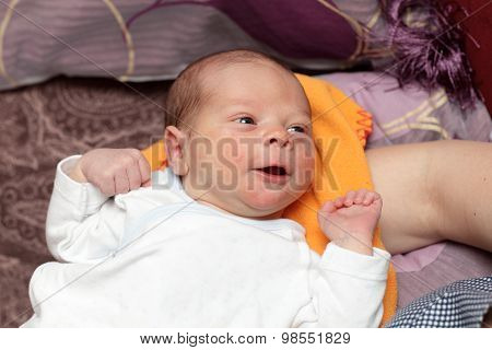 Smiling Newborn Lying On The Bed