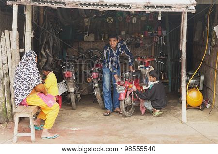 People fix motorbike in a workshop in Puthia, Bangladesh.