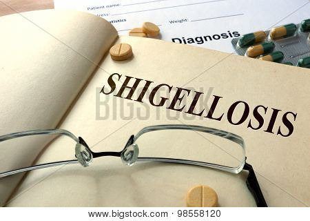 Word  Shigellosis on a paper and pills.