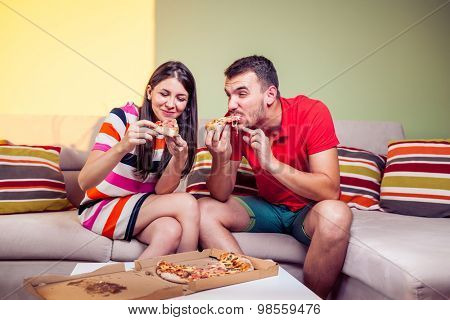 Funky young couple eating pizza on a couch in front of a green wall