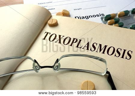 Word  Toxoplasmosis on a paper and pills.