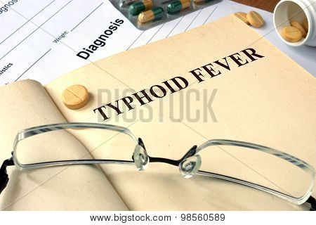 Word  Typhoid Fever on a paper and pills.