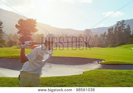 golfer takes a shot from the fairway in the morning sunshine on summer vacation