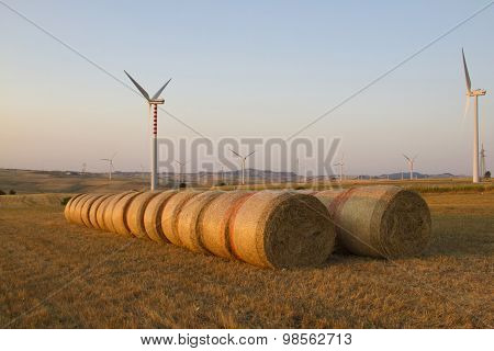 Wind Turbines And Bales Of Hay In A Field