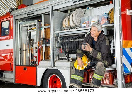 Happy fireman looking away while sitting in truck at fire station