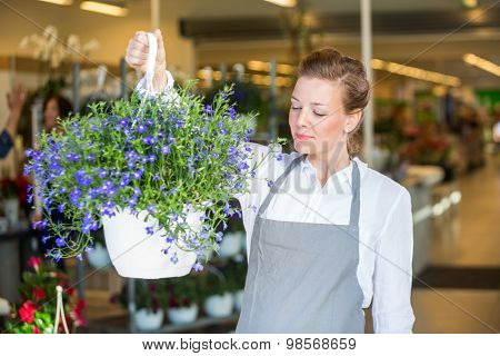 Beautiful mid adult female florist smelling purple flowers in shop