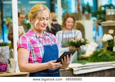 Smiling mature female florist using digital tablet with colleague working in background at shop