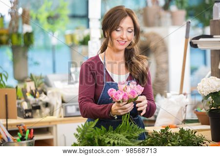 Happy florist making bouquet of pink roses in flower shop