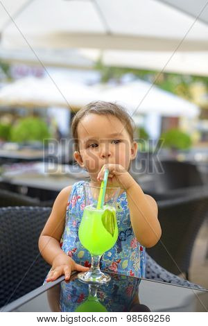 Little Girl Is Drinking  Lemonade With Mint Using Straw