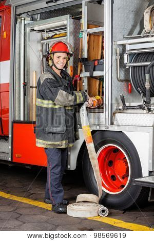 Portrait of happy firefighter adjusting hose in truck at fire station