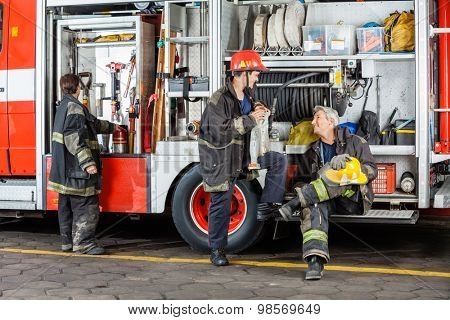 Full length of male firefighters discussing by truck at fire station