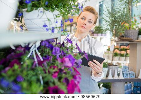 Portrait of mid adult florist holding digital tablet while standing by flower trolley in shop