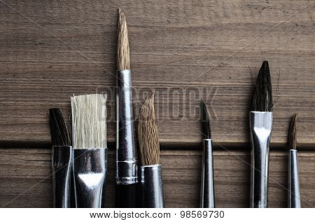 Artist Paintbrushes Overhead On Wood Planks