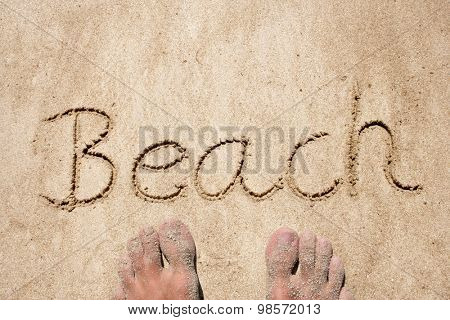 Beach hand written in sand on a beach on an exotic island background with feet for summer
