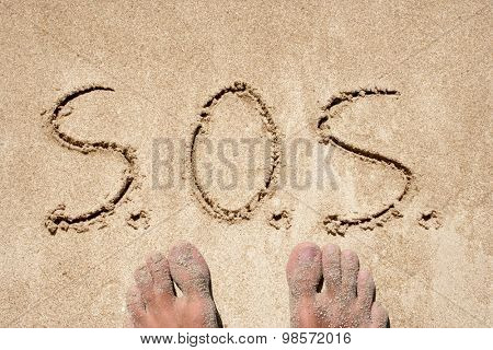 Concept or conceptual S.O.S. handwritten in sand for natural, symbol, tourism or conceptual designs background with feet