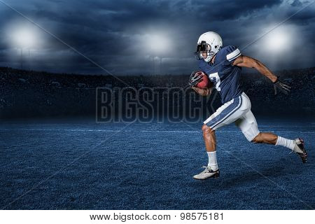 American Football Player Running for a touchdown in a large outdoor professional football stadium at
