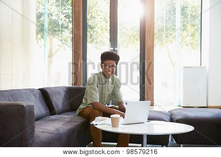 Portrait Of Businessman Having Working Lunch In Office