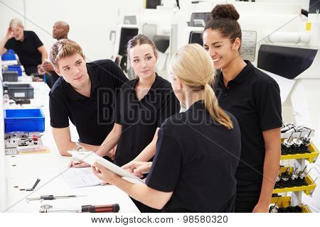 Engineer In Factory With Apprentices Checking Components