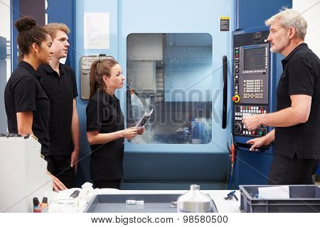 Three Apprentices Working With Engineer On CNC Machinery