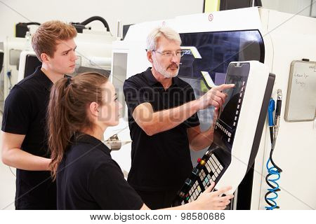 Two Apprentices Working With Engineer On CNC Machinery
