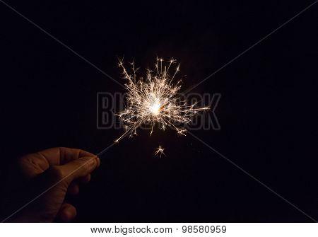 Hand Holding A Sparkler Fire On Black Background