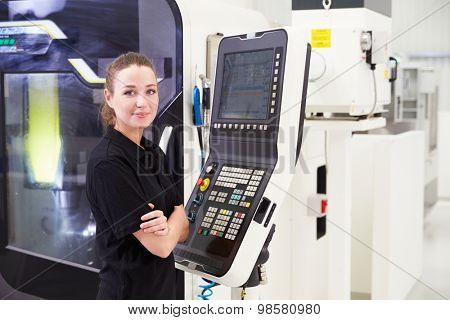 Portrait Of Female Engineer Operating CNC Machinery