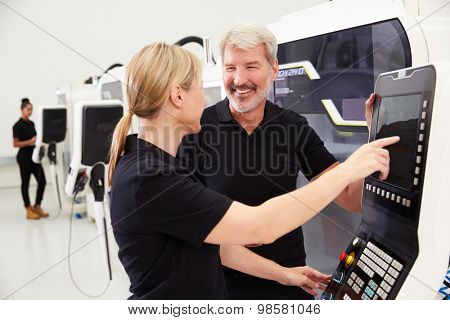Two Engineers Operating CNC Machinery On Factory Floor