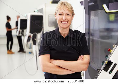 Portrait Of Female Engineer Operating CNC Machinery