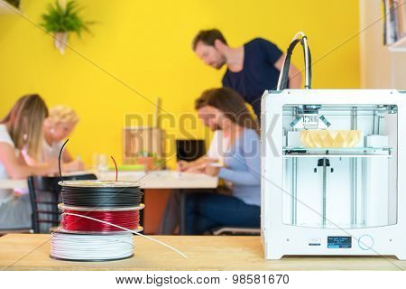 3D printer with product on counter with designers working in background at creative studio