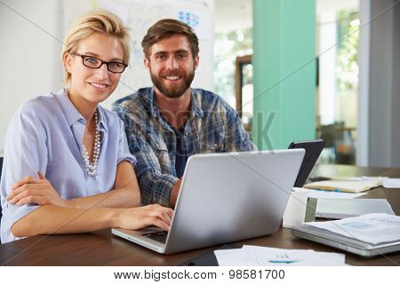 Two Businesspeople Working On Laptop In Office Together