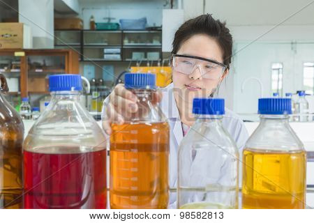 Asian Scientist Selecting Bottle In Shelf At Laboratory
