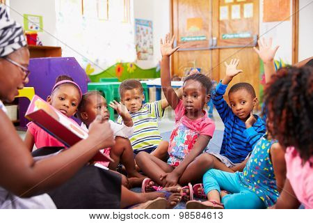 Class of preschool children raising hands to answer teacher