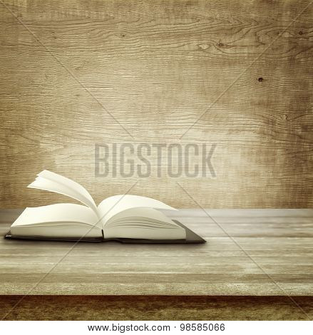 Open book on table in front of wooden wall