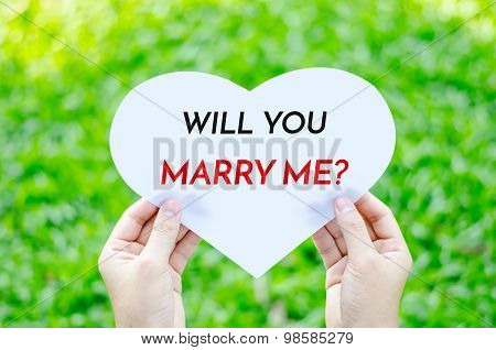 Hand Holding White Heart Paper With Will You Marry Me Text On Blur Green Grass Background