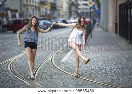 Two girls girlfriends walk along the tram tracks and fooling around in evening old town.