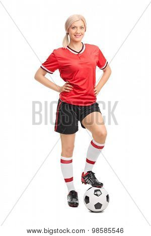 Full length portrait of a female soccer player in red jersey posing with a soccer ball under her foot isolated on white background