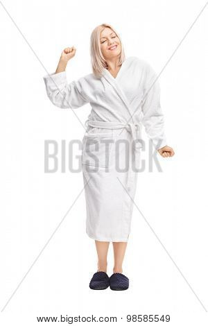 Full length portrait of a young blond woman in a white bathrobe stretching herself isolated on white background