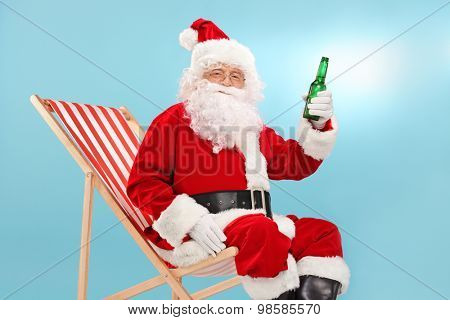 Santa Claus holding a bottle of beer seated on a sun lounger and looking at the camera with blue sky in the background