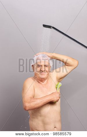 Vertical shot of a senior with a shower cap taking a shower and scrubbing himself with a bath brush