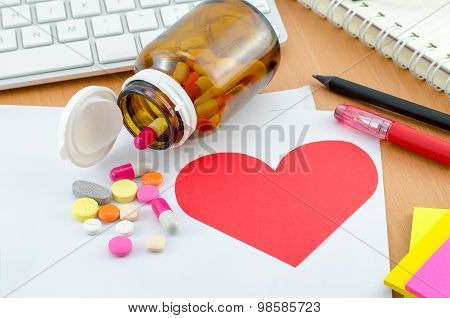 Health Care Concept - Red Heart Note Paper With Supplement On Computer Desk