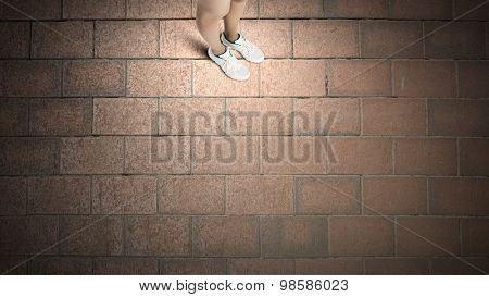 Top view of female legs in white sport shoes