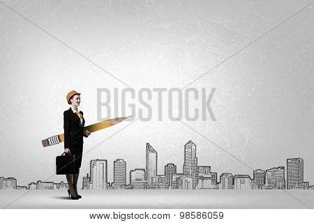 Young female engineer in hard hat with big pencil