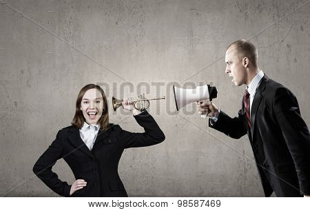 Businessman using megaphone to scream agressively at woman