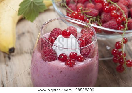 Smoothie Of Banana, Raspberry And Red Currant Decorated Ice Cream And Berries In A Glass.