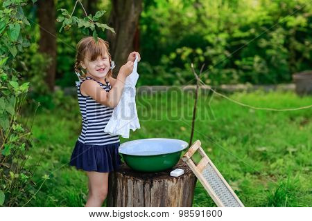 Little Helper Girl Washes Clothes In A Basin Outdoors