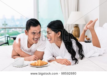 Asian couple having breakfast in bed with croissant and coffee