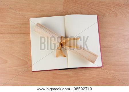 HIgh angle view of an open school book with a parchment diploma rolled and tied with a gold ribbon laying across the blank pages. Horizontal format on a wood desk.