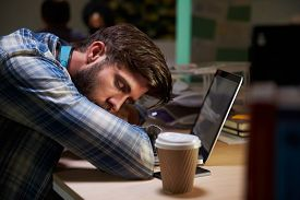 foto of late 20s  - Male Office Worker Asleep At Desk Working Late On Laptop - JPG