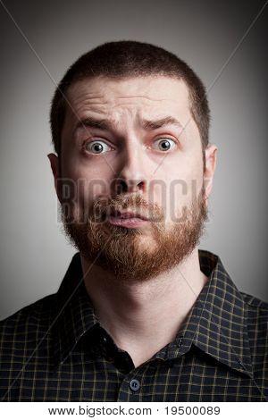 Face of funny amazed guy isolated on gray background