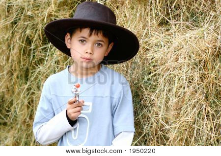 Young Boy Poses As Cowboy In Leather Hat